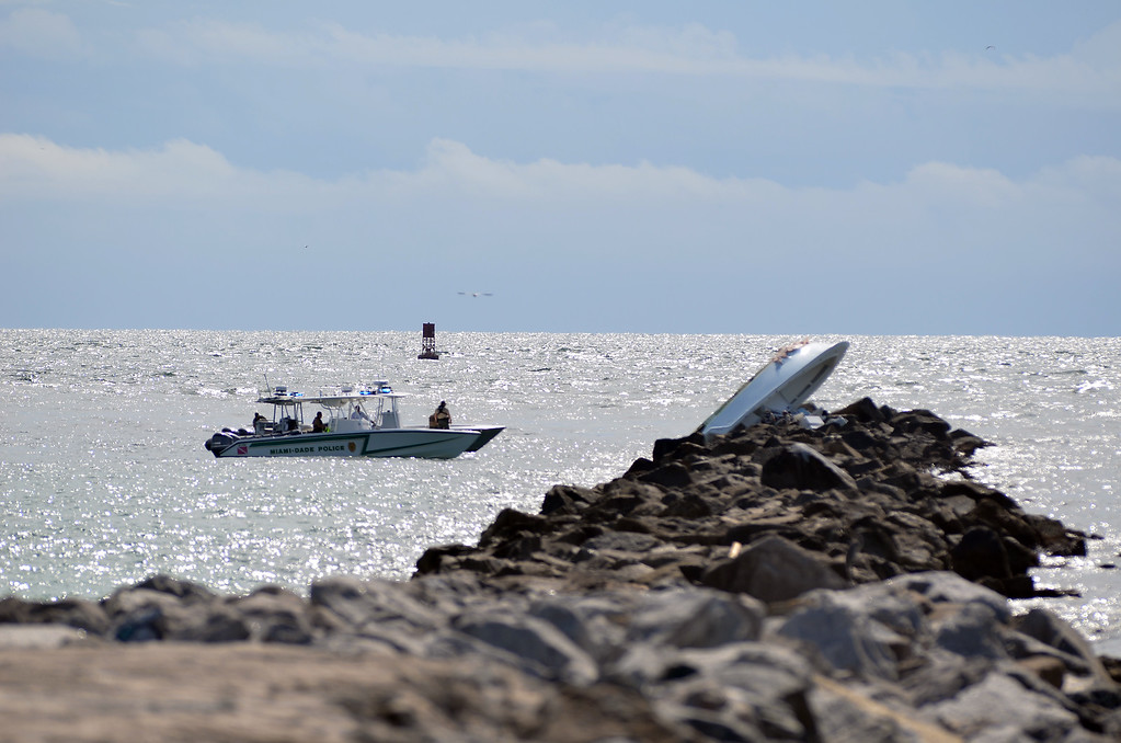 . Authorities continue their work at a boat overturned on a jetty, Sunday, Sept. 25, 2016, off Miami Beach, Fla. Authorities said that Miami Marlins starting pitcher Jose Fernandez was one of three people killed in the boat crash early Sunday morning. Fernandez was 24. (AP Photo/Gaston De Cardenas)
