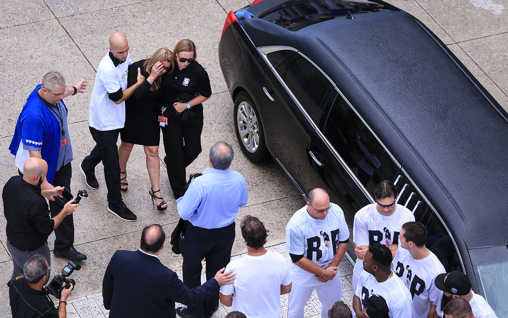 . MIAMI, FL - SEPTEMBER 28: Miami Marlins owner Jeffrey Loria, center in blue shit, and manager Don Mattingly, bottom center, await the late Jose Fernandez\' mother Maritza Fernandez, center top, as Miami Marlins players and members of the Marlins organization and their fans surround the hearse carrying Miami Marlins pitcher Jose Fernandez to pay their respects on September 28, 2016 in Miami, Florida. Mr. Fernandez was killed in a weekend boat crash in Miami Beach along with two friends. (Photo by Rob Foldy/Getty Images)