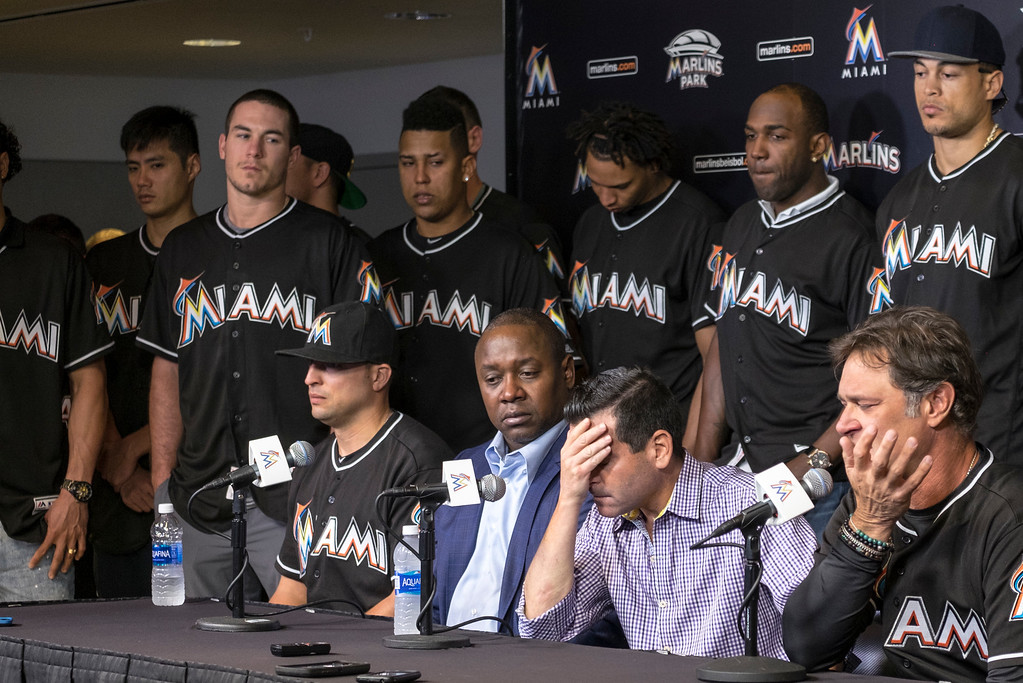 . David P. Samson, center, president of the Miami Marlins, covers his face during press conference to announce the death of Marlins pitcher Jose Fernandez. Fernandez, the ace right-hander for the Miami Marlins who escaped Cuba to become one of baseball\'s brightest stars, was killed in a boating accident early Sunday morning. Fernandez was 24. (AP Photo/Gaston De Cardenas)
