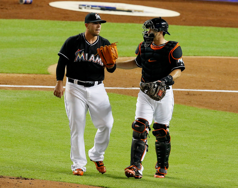 . Miami Marlins starting pitcher Jose Fernandez, left, speaks with Miami Marlins catcher J.T. Realmuto  in the second inning of play against the New York Mets during a baseball game in Miami, Saturday, July 23, 2016. (AP Photo/Joe Skipper)