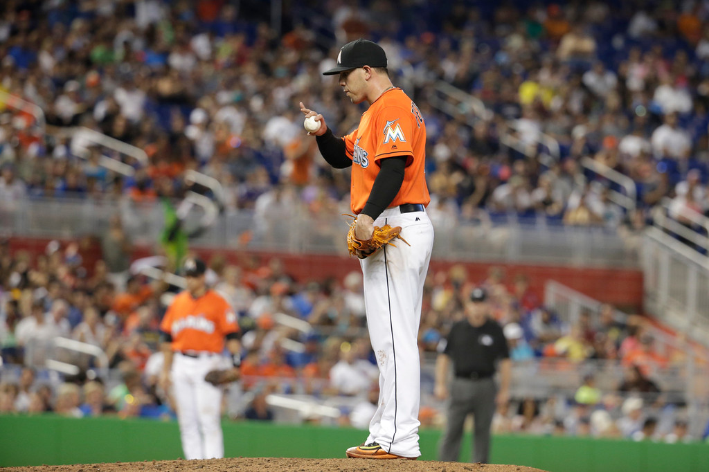 . Miami Marlins starting pitcher Jose Fernandez blows on the ball during a baseball game against the Chicago Cubs, Sunday, June 26, 2016, in Miami.  (AP Photo/Lynne Sladky)