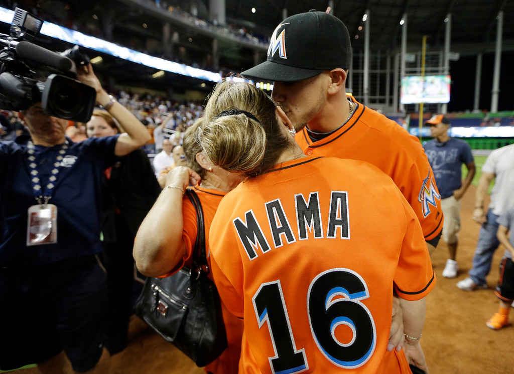 . Miami Marlins starting pitcher Jose Fernandez, right, kisses his mother Martiza Fernandez, of Miami, after the Marlins defeated the Colorado Rockies 10-1 in an opening day baseball game, Monday, March 31, 2014, in Miami. (AP Photo/Lynne Sladky)