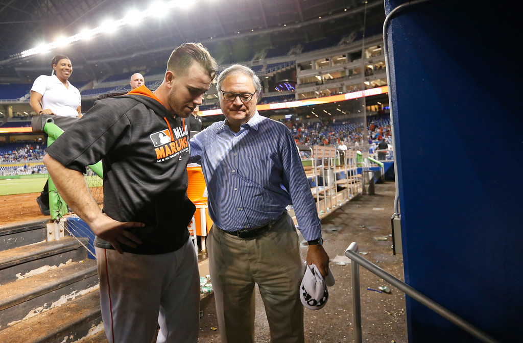 . Miami Marlins starting pitcher Jose Fernandez, left, leaves the dugout with Marlins owner and CEO Jeffrey Loria, after the Marlins defeated the Los Angeles Dodgers during a baseball game, Friday, Sept. 9, 2016, in Miami.  (AP Photo/Wilfredo Lee)
