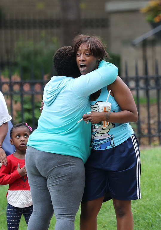 """. Shouting:\""""I want justice, I want peace,\"""" Diamond Reynolds, right, the girlfriend of Philando Castile, is hugged by Leigh Ross of Roseville as Reynolds arrives at a protest outside The Governors Residence with her unidentified child Thursday, July 7, 2016, in St. Paul, Minn.  Philando Castile was shot in a car by police Wednesday night in the St. Paul suburb of Falcon Heights. Police have said the incident began when an officer initiated a traffic stop in suburban Falcon Heights but have not further explained what led to the shooting. (David Joles/Star Tribune via AP)"""