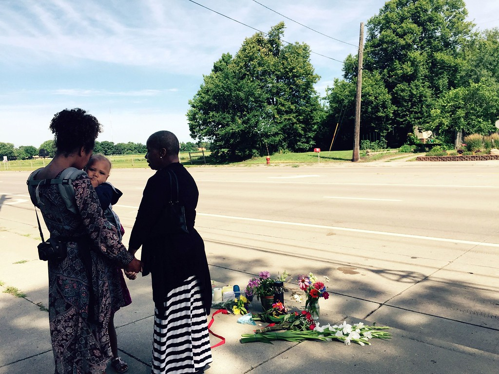 . Pastor Patricia Bell (R) of St. Paul, Minnesota, prays on July 7, 2016, with Gabriella Dunn and her children Oakland Dunn, 1, and Chloe Dunn, 4, at the scene of the latest shooting of a black man by police in Falcon Heights, Minessota Philando Castile was shot by police after being pulled over while driving. The incident was captured in a video viewed by some two million people Thursday, as civil rights investigators probed a similar incident in Louisiana.  (JOY POWELL/AFP/Getty Images)