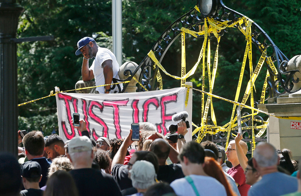 . A man, top left, stands alone on the wall outside the governor\'s residence as police tape covers the gate Thursday, July 7, 2016, in St. Paul, Minn. as protesters gathered to on condemn the shooting death by police of Philando Castile Wednesday night in Falcon Heights, Minn. after a traffic stop by St. Anthony police. AP Photo/Jim Mone)