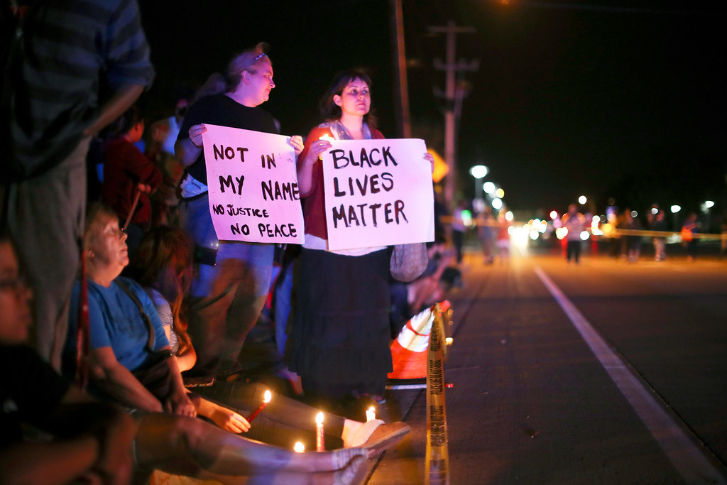 . Demonstrators hold signs across the street from the scene of a Wednesday night shooting in Falcon Heights, Minn., Thursday, July 7, 2016. Philando Castile was shot in a car Wednesday night in the largely middle-class St. Paul suburb of Falcon Heights. Police have said the incident began when an officer initiated a traffic stop in suburban Falcon Heights but have not further explained what led to the shooting. (Jeff Wheeler/Star Tribune via AP)