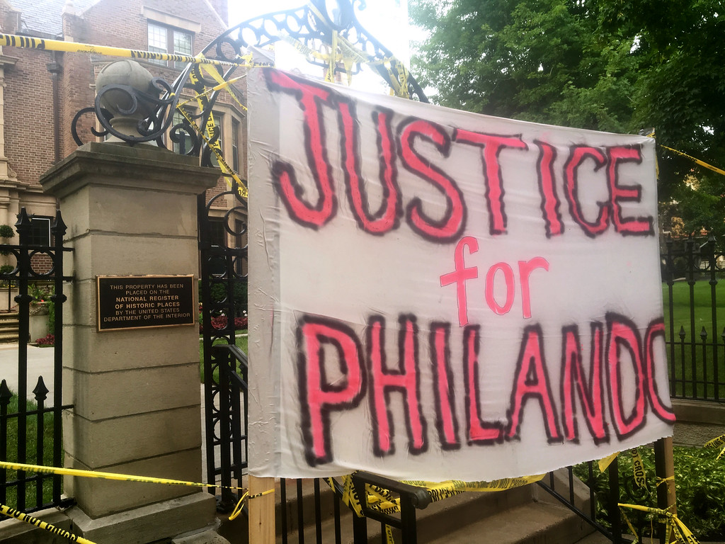 . A sign is hung outside the Minnesota Governor\'s Residence as about 200 people gathered in St. Paul, Thursday, July 7, 2016, protesting the fatal shooting of a man by a suburban police officer. Philando Castile was shot in a car Wednesday night in the largely middle-class St. Paul suburb of Falcon Heights. Police have said the incident began when an officer initiated a traffic stop in suburban Falcon Heights but have not further explained what led to the shooting.  (AP Photo/Jeff Baenen)