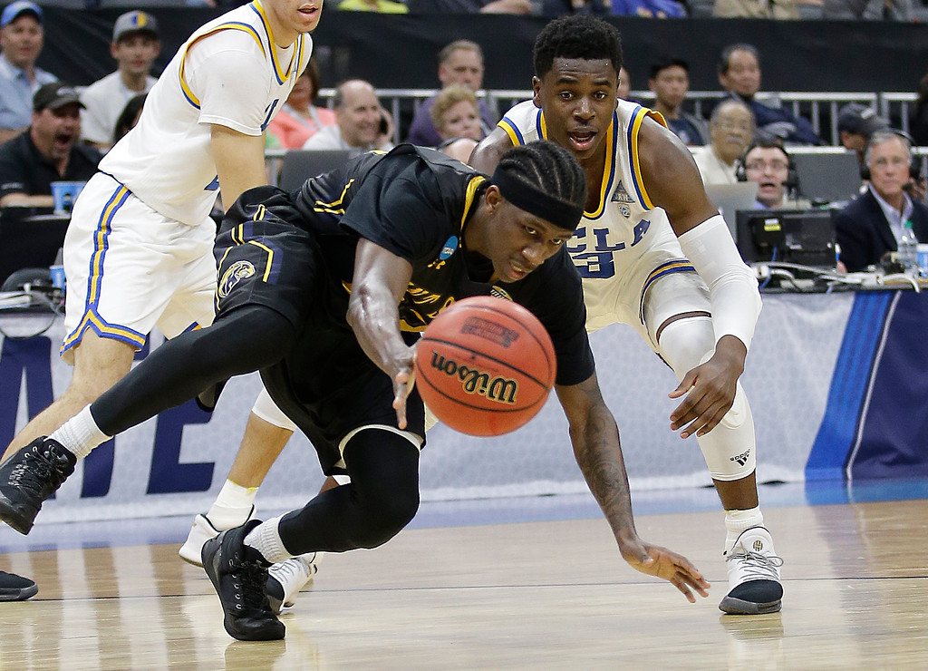 . Kent State guard Jaylin Walker, left, and UCLA guard Aaron Holiday scramble for the ball during the second half of a first-round game of the men\'s NCAA college basketball tournament in Sacramento, Calif., Friday, March 17, 2017. UCLA won 97-80. (AP Photo/Rich Pedroncelli)