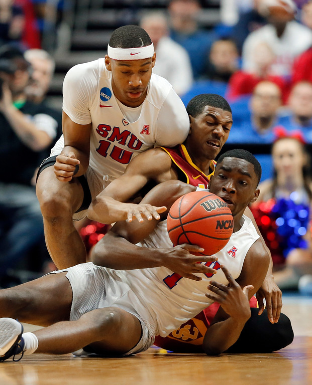 . SMU\'s Jarrey Foster (10) and Shake Milton (1) scramble on the court floor for a loose ball against USC\'s De\'Anthony Melton, center, in the first half of a first-round game in the men\'s NCAA college basketball tournament in Tulsa, Okla., Friday March 17, 2017. (AP Photo/Tony Gutierrez)