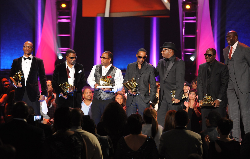 . LAS VEGAS, NV - NOVEMBER 8: Ronnie Devoe, Ricky Bell, Michael Bivens, Bobby Brown, Ralph Tresvant, and Johnny Gill of New Edition accept the Soul Train Lifetime Achievement Award from Earvin Magin Johnson onstage at the Soul Train Awards 2012 at PH Live at Planet Hollywood Resort & Casino on November 8, 2012 in Las Vegas, Nevada. (Photo by Frank Micelotta/PictureGroup) via AP IMAGES