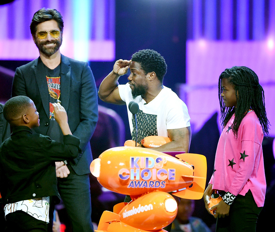 . LOS ANGELES, CA - MARCH 11:  Actor Kevin Hart (C) accepts the awards for Most Wanted Pet and Favorite Villain for The Secret Life of Pets from John Stamos onstage at Nickelodeon\'s 2017 Kids\' Choice Awards at USC Galen Center on March 11, 2017 in Los Angeles, California.  (Photo by Kevin Winter/Getty Images)