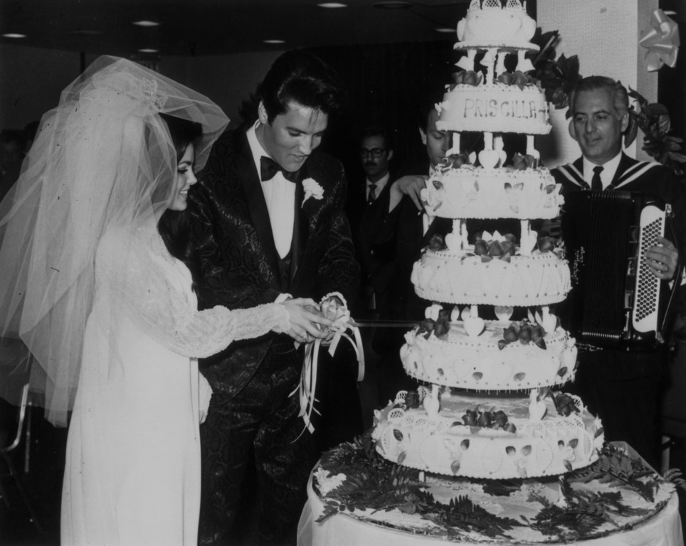 . Elvis Presley (1935 - 1977) cutting the six-tier wedding cake with his bride Priscilla Beaulieu at the Aladdin Hotel, Las Vegas.   (Photo by Keystone/Getty Images)