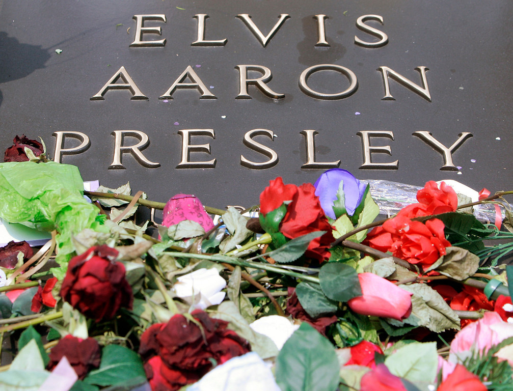 . FILE - In this Aug. 16, 2007 file photo, the grave of Elvis Presley is covered with flowers on the grounds of Graceland in Memphis, Tenn., on the 30th anniversary of his death. (AP Photo/Mark Humphrey, file)