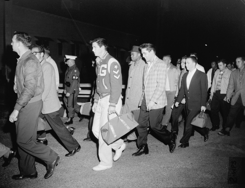 . Singer Elvis Presley, in checkered sport coat, and other recruits are shown in their first Army maneuver, a walk from a bus to a supply building where they received their first G.I. issue bedding for the night.  Elvis and 21 others arrived at Fort Chaffee, Arkansas by bus on March 24, 1958 from Memphis, Tennessee, where they were inducted.  (AP Photo)