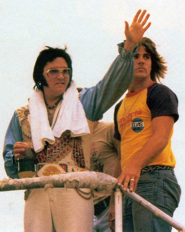 ". In this 1976 photo released by Impello Films,  Elvis Presley waves as his stepbrother D. Edward Stanley  looks as they board a plane while on tour. On the brink of the 30th anniversary of Presley\'s passing, and the DVD release of Stanley\'s autobiographical drama ""Protecting the King,\"" the filmmaker talked to The Associated Press about living with Presley, witnessing his death and protecting his memory. (AP Photos/Impello Films)"