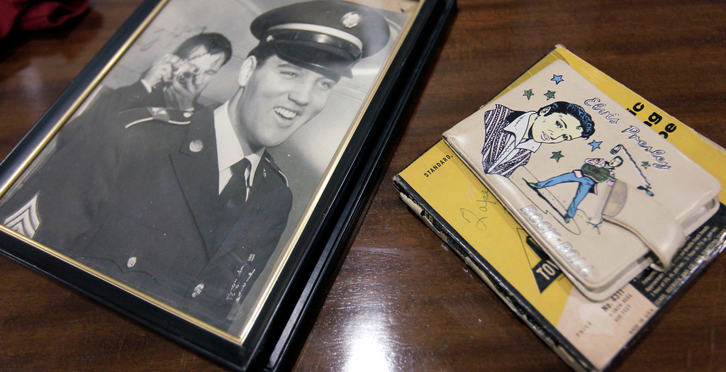 . An autographed photo of Elvis Presley in his Army uniform and an Elvis Presley Enterprises Rock \'n\' Roll vinyl billfold are two of over 200 items in The Gary Pepper Collection of Elvis Presley Memorabilia at Leslie Hindman Auctioneers, Monday, Oct. 12, 2009, in Chicago.   (AP Photo/M. Spencer Green)