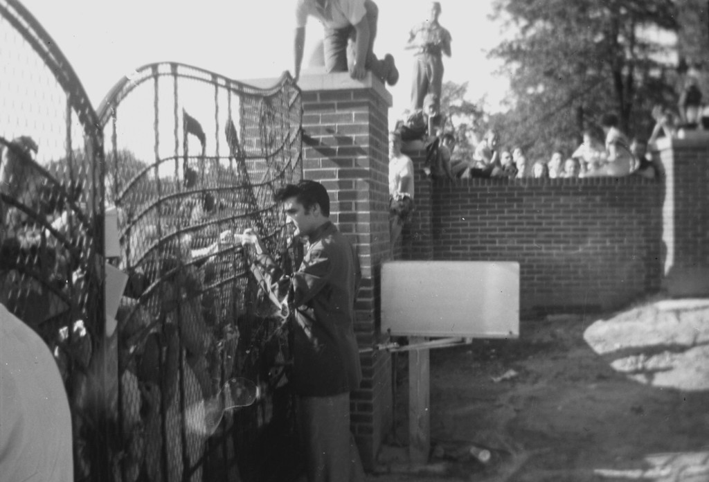. In this 1957 photo provided by Elvis Presley Enterprises, Inc and used by permission,  Elvis Presley greets fans at the gates of Graceland in Memphis, Tenn. Elvis Presley archivists have found three rare photos dating back to 1957 that show the young singer greeting fans at the gates of Graceland. Negatives of the photos were discovered as archivists pored through a vast collection of documents from the office of Vernon Presley, Elvis\' father. (AP Photo/Elvis Presley Enterprises, Inc)