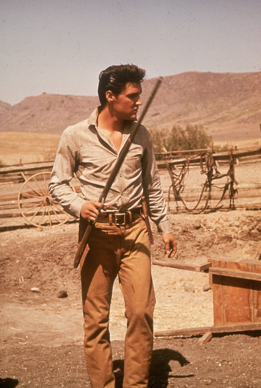 . American film star Elvis Presley (1935 - 1977) strides around a ranch with a gun in his hand.   (Photo by Hulton Archive/Getty Images)