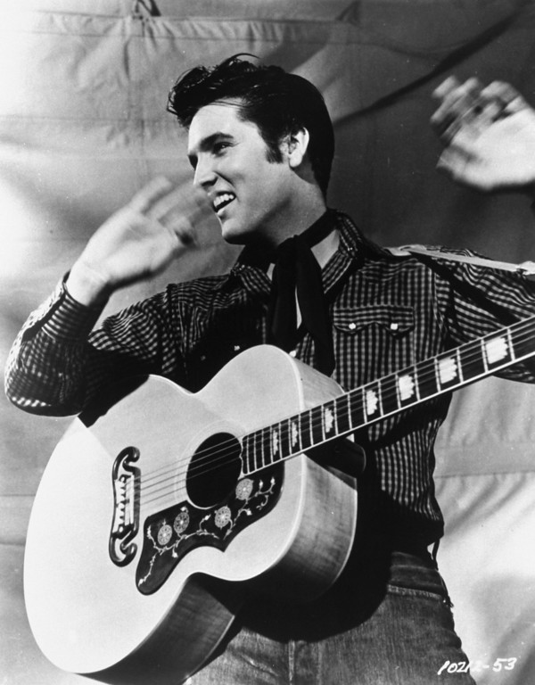 . Elvis Presley poses with his Gibson J-200 guitar in an MGM studio publicity photo from the 1950s.    (AP Photo/MGM, File )