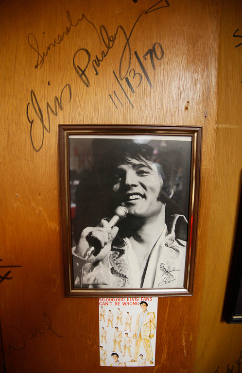 . Elvis Presley\'s signature is shown above his photograph on a wall inside the box office at the Cow Palace in San Francisco, Friday, July 2, 2010. The box office wall\'s are filled with signatures by many who have performed in the exposition hall.  (AP Photo/Eric Risberg)