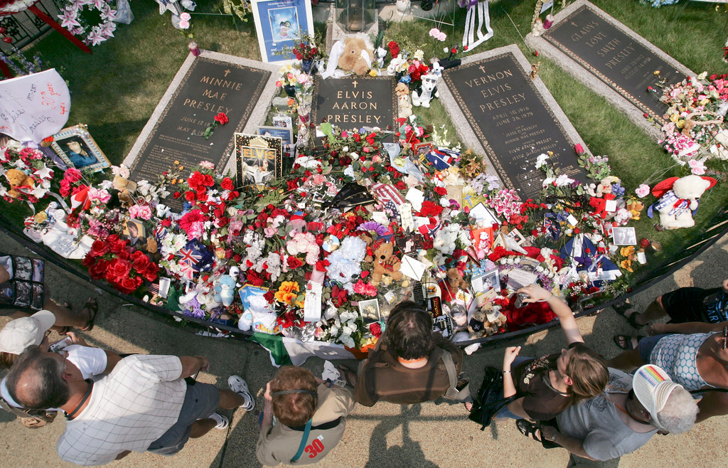 . Fans walk by the flower-covered grave of Elvis Presley on the grounds of Graceland in Memphis, Tenn., on the 30th anniversary of his death Thursday, Aug. 16, 2007. Presley is buried between his grandmother, Minnie Mae, and his father, Vernon. The grave of his mother, Gladys, is at right. (AP Photo/Mark Humphrey)