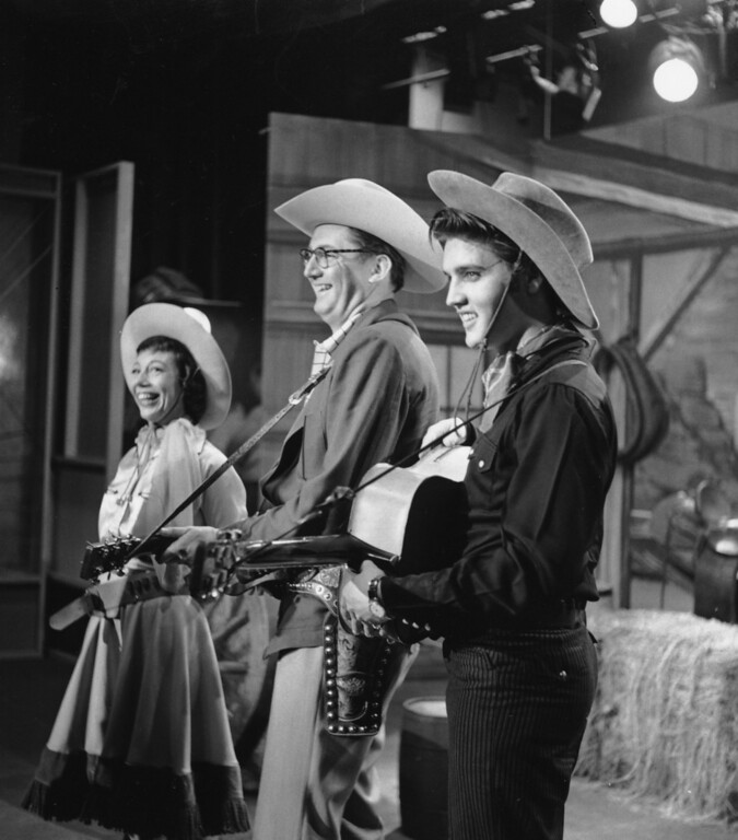 ". Singer Elvis Presley is shown performing on the television program ""The Steve Allen Show\"" at the Hudson Theatre in New York, in this July 1956, file photo.  At center is Steve Allen and to his right is Imogene Coca. Elvis fans from around the world are in Memphis this week for the annual remembrance of his death in 1977, and many still remember the year Elvis lit up American televisions.  (AP Photo/FILE)"