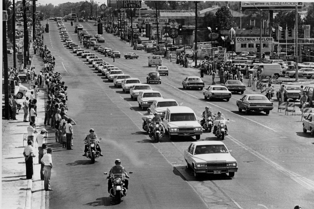 . A string of white vehicles follow the hearse carrying the body of rock and roll musician Elvis Presley along Elvis Presley Boulevard on the way to Forest Hills Cemetery in Memphis, Tenn., Aug. 19, 1977.  (AP Photo)