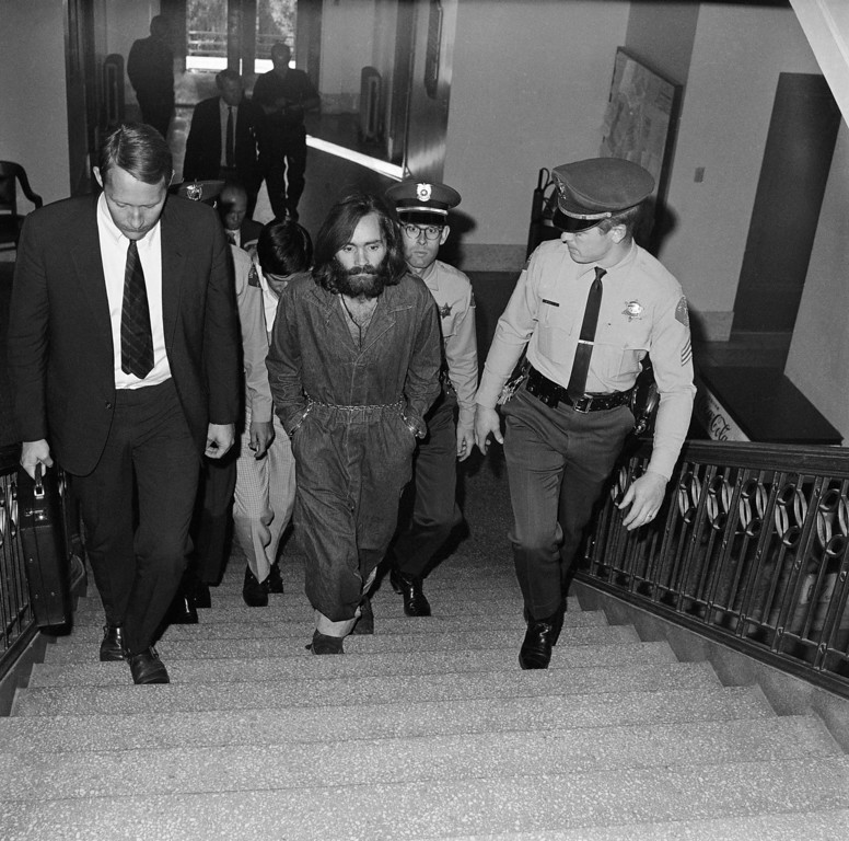 . Charles Manson, hippie cult leader, is led upstairs to court in Independence, Calif., Dec. 3, 1969. At left is public defender Fred Schaefer. (AP Photo/Harold Filan)
