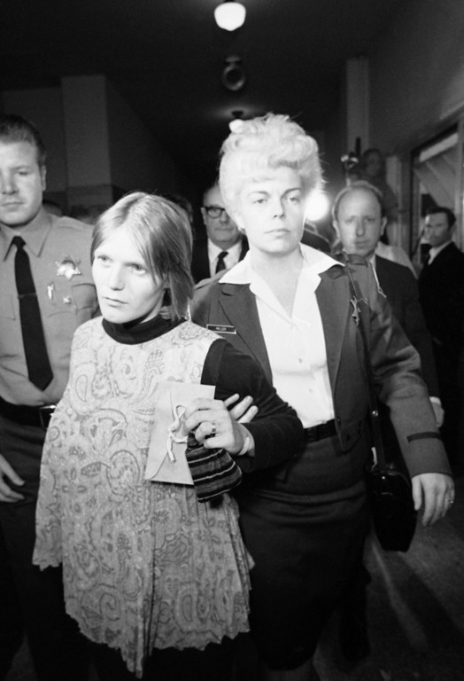 . Linda Louise Kasabian, left, brought to Los Angeles from Concord, New Hampshire, where she surrendered on a murder warrant, is led down a corridor on Dec.4, 1969 of the Los Angeles Hall of Justice after her arraignment in Los Angeles. The girl, mother of an 18-month-old baby and five months pregnant, is one of three persons arrested in the slayings of Sharon Tate and others. (AP Photo/Wally Fong)