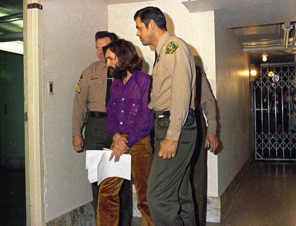 . Charles Manson, cult leader charged in the Tate-LaBianca murder case, is led to court by guards, in 1969.  (AP Photo)