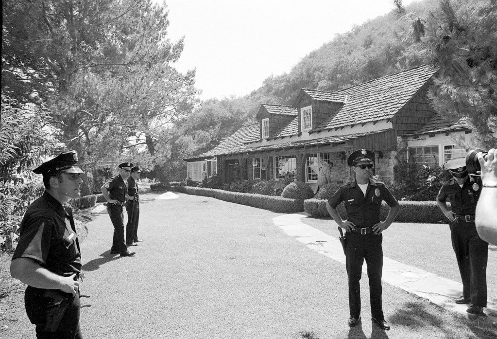 . Police officers stand on the property of actress Sharon Tate where the bodies of five persons, including Tate, were found murdered by members of the Manson cult family, August 9, 1969.  (AP Photo)