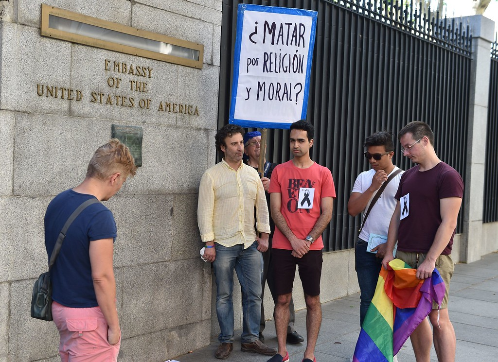 ". People with a rainbow flag stand in front of the embassy of the United States in Madrid, to pay tribute to the victims of the shooting of Orlando, on June 12, 2016. Fifty people died and another 53 were injured when a gunman opened fire and seized hostages at the Pulse, a gay nightclub in Orlando, Florida, police said June 12, making it the worst mass shooting in US history. Placard reads: ""Killing for religion and moral?\"" (GERARD JULIEN/AFP/Getty Images)"