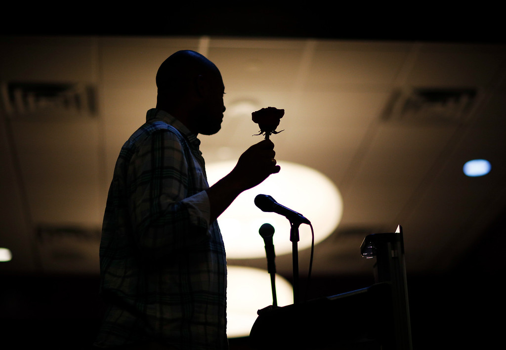 . Nevada state Senator Aaron Ford holds a rose during a prayer vigil at The Center, a community center for the LGBT community, Sunday, June 12, 2016, in Las Vegas. The vigil was for the victims of the Pulse nightclub shooting in Orlando. (AP Photo/John Locher)