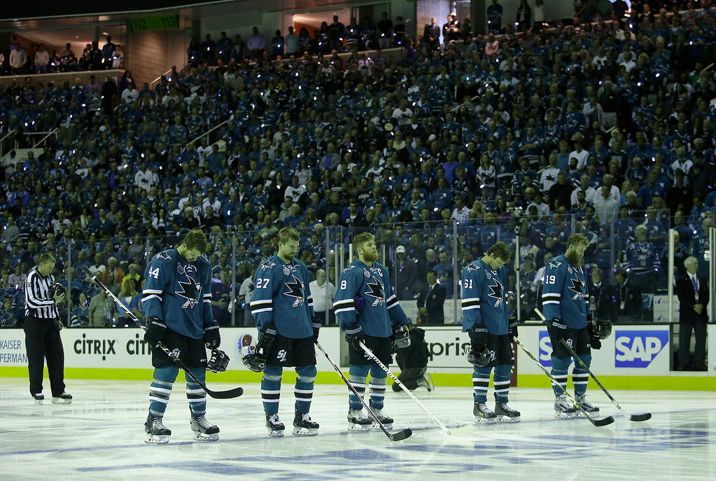 . San Jose Sharks players stand during a moment of silence for the victims of the mass shooting in Orlando, Fla., before Game 6 of the NHL hockey Stanley Cup Finals between the Sharks and the Pittsburgh Penguins in San Jose, Calif., Sunday, June 12, 2016. (AP Photo/Marcio Jose Sanchez)