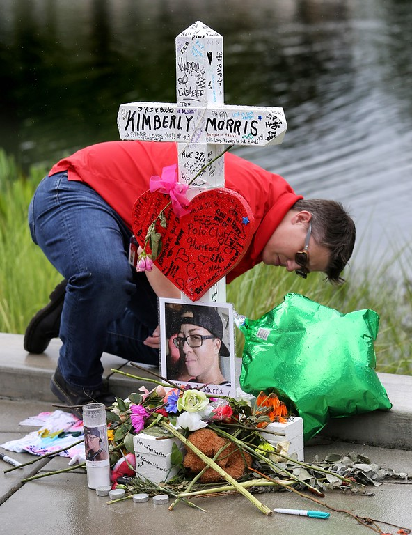. A visitor signs one of the 49 crosses at a makeshift memorial outside Orlando Regional Medical Center, Sunday , June 19, 2016. The crosses were erected by an Illinois man to honor each of the victims in the Pulse massacre.  (Joe Burbank/Orlando Sentinel via AP)