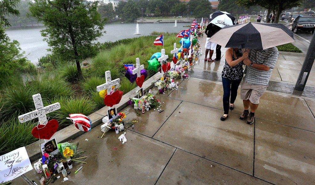 . Visitors brave the rain to view the 49 crosses at  the makeshift memorial outside Orlando Regional Medical Center, Sunday, June 19, 2016. The crosses were erected by an Illinois man to honor each of the victims in the Pulse massacre. (Joe Burbank/Orlando Sentinel via AP)