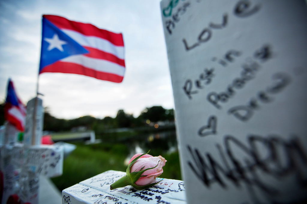 . A rose sits on a cross honoring Christopher Andrew Leinonen and the fellow victims of the Pulse nightclub mass shooting a week ago at a makeshift memorial early Sunday, June 19, 2016, in Orlando, Fla. (AP Photo/David Goldman)