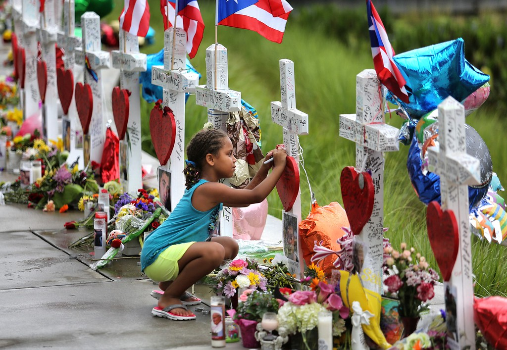 . Seven-year-old Mekiha Thomas of Orlando signs one of the 49 crosses at a makeshift memorial outside Orlando Regional Medical Center, Sunday, June 19, 2016. The crosses were erected by an Illinois man to honor each of the victims in the Pulse massacre. (Joe Burbank/Orlando Sentinel via AP)