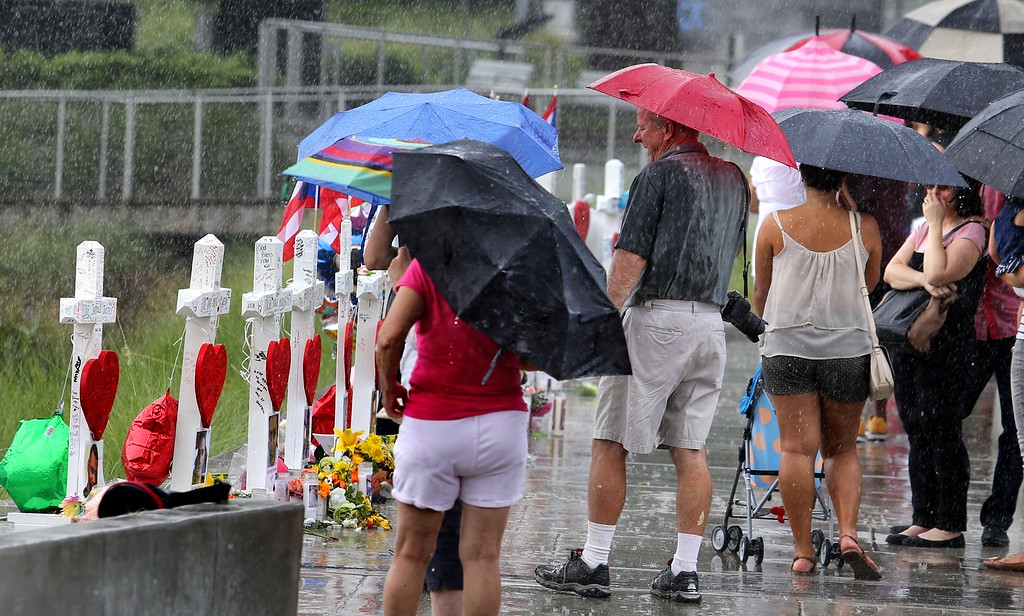. Visitors brave the rain to view the 49 crosses at  the makeshift memorial outside Orlando Regional Medical Center, Sunday , June 19, 2016. The crosses were erected by an Illinois man to honor each of the victims in the Pulse massacre. (Joe Burbank/Orlando Sentinel via AP)