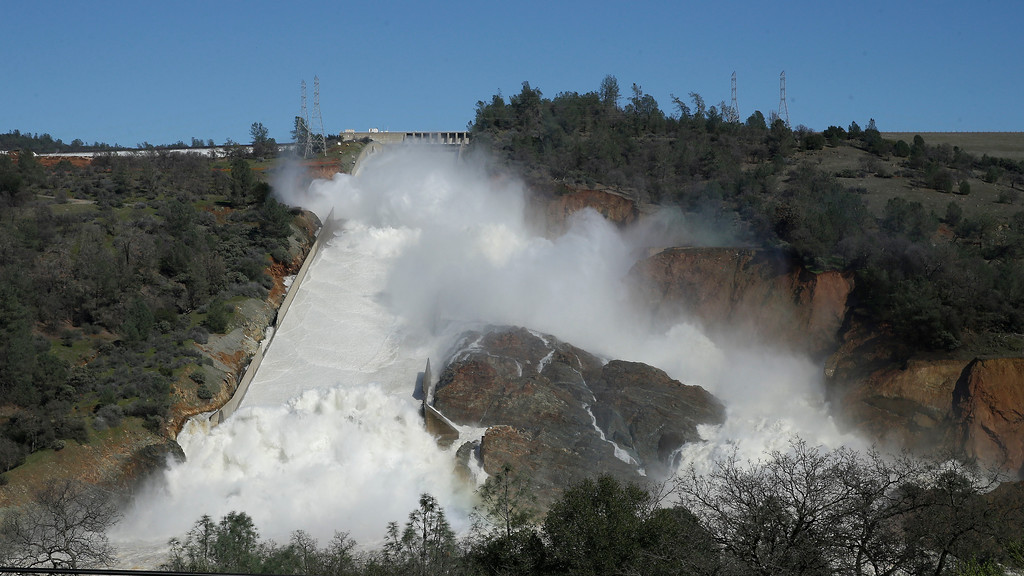 """. In this Saturday, Feb. 11, 2017, water flows down Oroville Dam\'s main spillway near Oroville, Calif. Officials have ordered residents near the Oroville Dam in Northern California to evacuate the area Sunday, Feb. 12, saying a \""""hazardous situation is developing\"""" after an emergency spillway severely eroded. (AP Photo/Rich Pedroncelli)"""