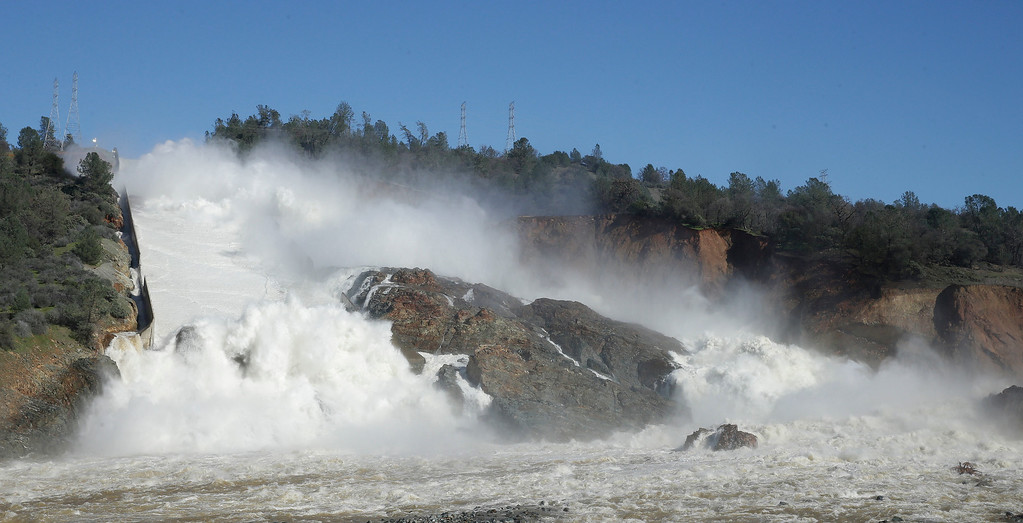 """. In this Saturday, Feb. 11, 2017, water flows down Oroville Dam\'s main spillway, near Oroville, Calif. Officials have ordered residents near the Oroville Dam in Northern California to evacuate the area Sunday, Feb. 12, saying a \""""hazardous situation is developing\"""" after an emergency spillway severely eroded. (AP Photo/Rich Pedroncelli)"""