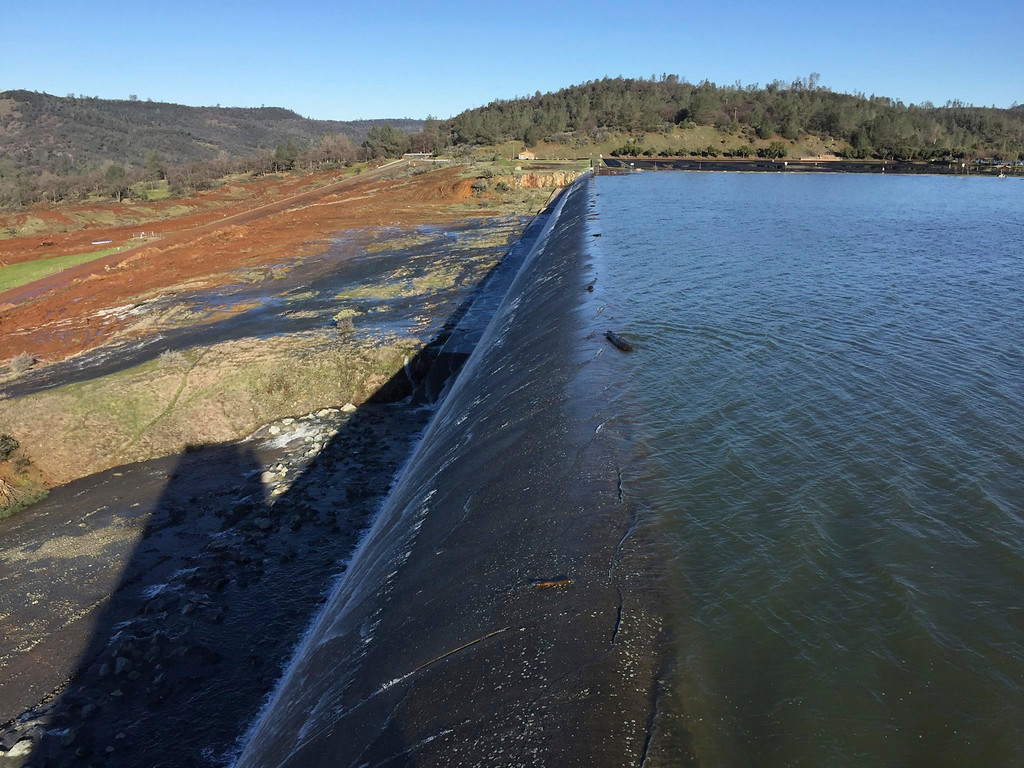 . In this Feb. 11, 2017, photo released by the California Department of Water Resources, water flows over an emergency spillway at the Oroville Dam at Lake Oroville in Oroville, Calif. Water will continue to flow over the emergency spillway at the nation\'s tallest dam for another day or so, officials said Sunday. (Albert Madrid/California Department of Water Resources via AP)