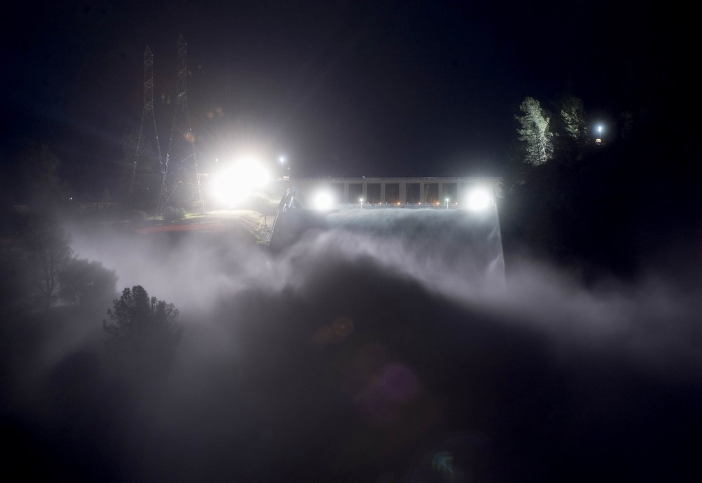 . This long exposure photograph shows the Oroville Dam discharging water at a rate of 100,000 cubic feet per second over a spillway as an emergency measure in Oroville, California on February 13, 2017. More than 100,000 people have been evacuated from low-lying areas after erosion damaged the emergency spillway to Lake Oroville which is currently at 101 percent capacity.  (JOSH EDELSON/AFP/Getty Images)