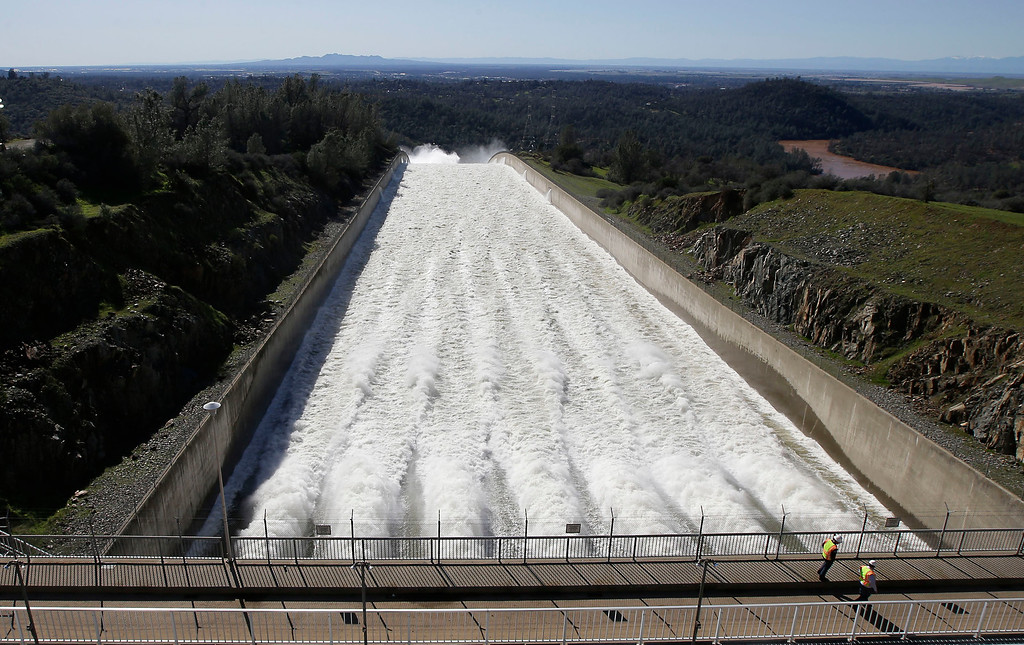 """. In this Saturday, Feb. 11, 2017, photo, water flows down Oroville Dam\'s main spillway, in Oroville, Calif. Officials have ordered residents near the Oroville Dam in Northern California to evacuate the area Sunday, Feb. 12, saying a \""""hazardous situation is developing\"""" after an emergency spillway severely eroded. (AP Photo/Rich Pedroncelli)"""