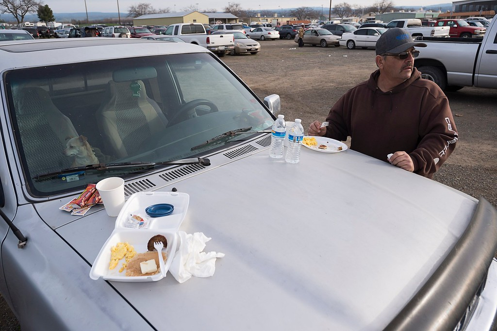 . Todd Remocal of Biggs, Calif., eats breakfast on the hood of his truck at the Silver Dollar Fairgrounds on Monday, Feb. 13, 2017, in Chico, Calif. He and his wife Kelly slept in their vehicle with their three dogs last night after residents were evacuated from the area due to fears of a possible failure of the emergency spillway at the Oroville Dam.(Paul Kitagaki Jr./The Sacramento Bee via AP)