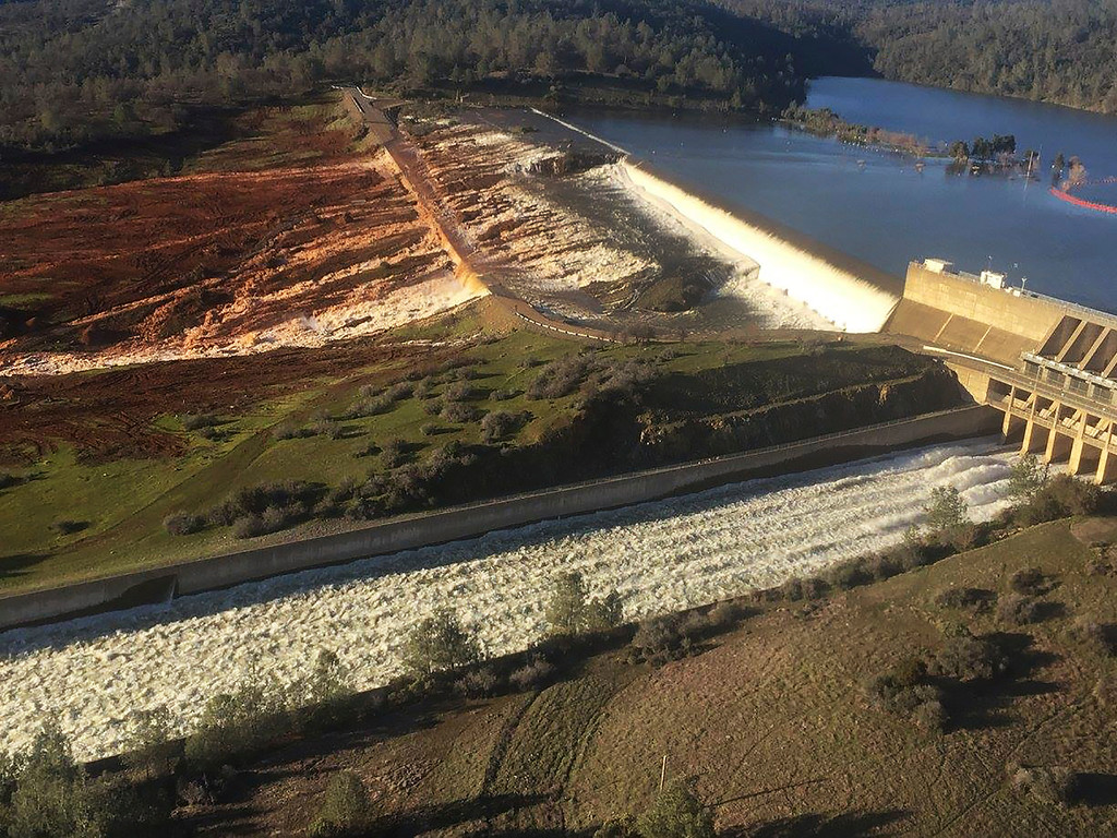 . This Feb. 11, 2017, photo released by the California Department of Water Resources shows the main spillway, bottom, and an auxiliary spillway, upper, of the Oroville Dam at Lake Oroville in Oroville, Calif. Water will continue to flow over the emergency spillway at the nation\'s tallest dam for another day or so, officials said Sunday. (Albert Madrid/California Department of Water Resources via AP)