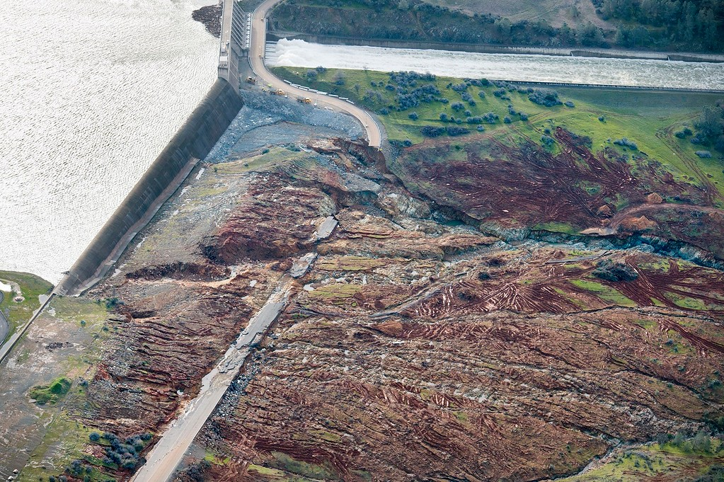 . In an aerial photo, the emergency spillway at Lake Oroville shows signs of damage from the water which spilled over recently, on Monday, Feb. 13, 2017, in Oroville, Calif. Sunday afternoon\'s evacuation order came after engineers spotted a hole on the concrete lip of the secondary spillway for the 770-foot-tall Oroville Dam and told authorities that it could fail within the hour. The water level dropped Monday behind the nation\'s tallest dam, reducing the risk of a catastrophic spillway collapse and easing fears that prompted the evacuation of nearly 200,000 people downstream.    (Randy Pench/The Sacramento Bee via AP)