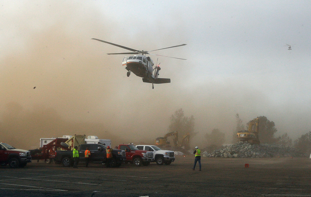 . A helicopter kicks up dust as it lands at a staging area near the Oroville Dam on Monday, Feb. 13, 2017, in Oroville, Calif. State officials have discussed using helicopters to drop loads of rock on the damaged emergency spillway of the dam. (AP Photo/Rich Pedroncelli)