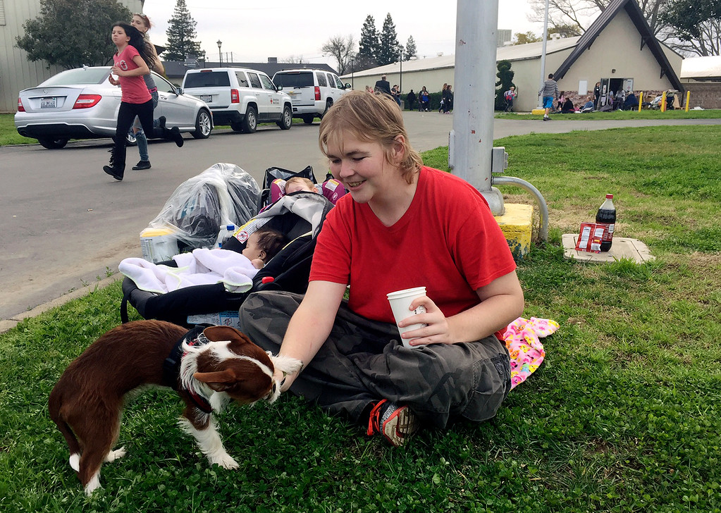 . Marcella Mooney plays with her dog while her daughter sleeps in a car seat at the Silver Dollar Fairgrounds, Monday, Feb. 13, 2017, in Chico, Calif. Mooney\'s family had to evacuate Oroville, Calif., yesterday and plan to stay at the fairgrounds another night. Thousands of people remain under evacuation orders after Northern California authorities warned an emergency spillway in the country\'s tallest dam was in danger of failing Sunday and unleashing uncontrolled flood waters on towns below. (AP Photo/Terrry Chea)